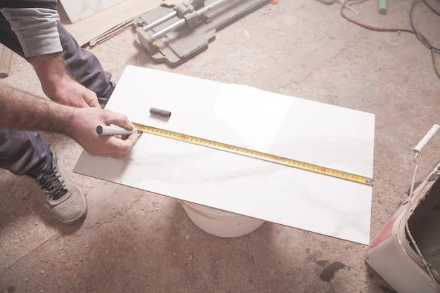Плиточник измеряет и отрезает плитку.