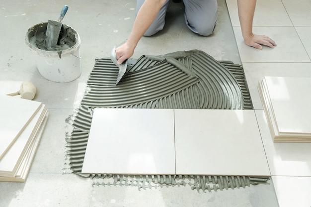 Плиточник наносит плитку на клей с помощью зубчатого шпателя