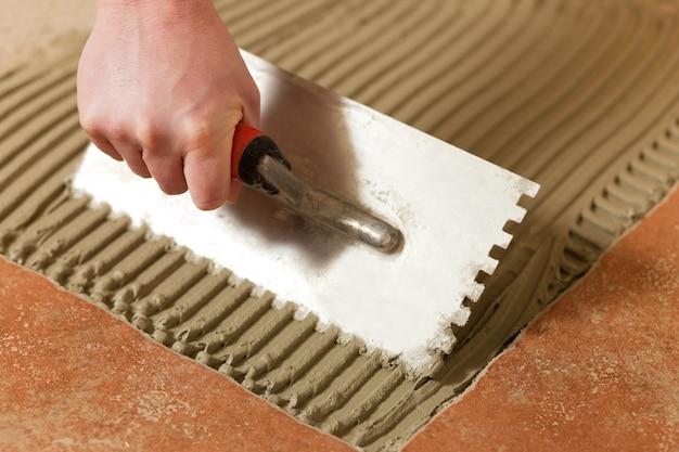 Tiler tiling tiles on the floor