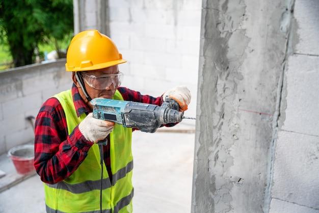 전기 충격 드릴을 사용하여 미완성 주택 건설에서 시멘트 벽을 시추하는 타일러