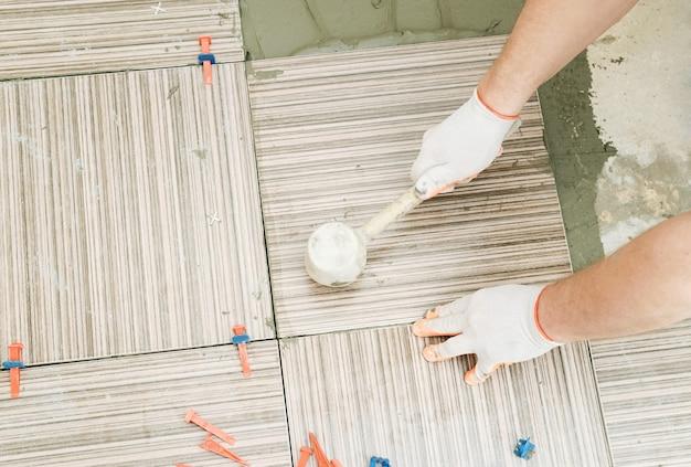 Плиточник с помощью резинового молотка для выравнивания керамической плитки
