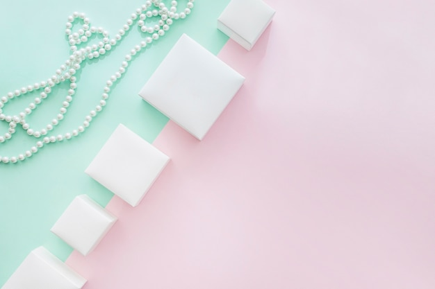 Tilt row of different white boxes with pearls necklace on pastel background