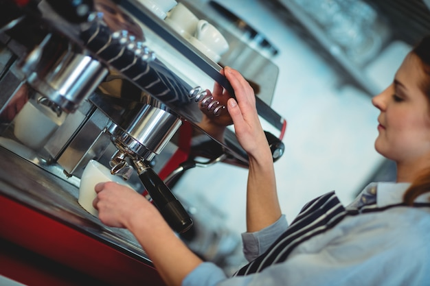 Tilt shot of barista using espresso machine to pour coffee in cup