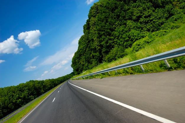 傾斜アングルショットは、美しい夏の自然に囲まれた滑らかな高速道路です
