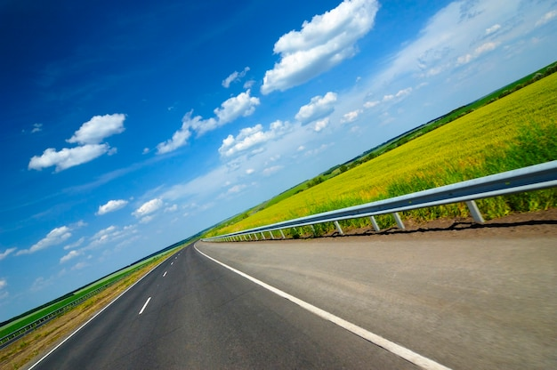 Tilted angle shot of a smooth highway surrounded by beautiful summer nature with green grass and fields on a sunny summer hot day