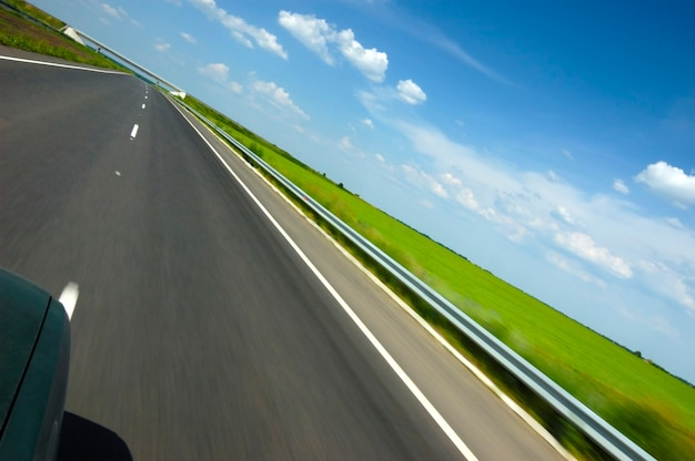 Tilted angled shot of a smooth highway surrounded by beautiful summer nature with green grass and blue sky with trees on a sunny summer hot day