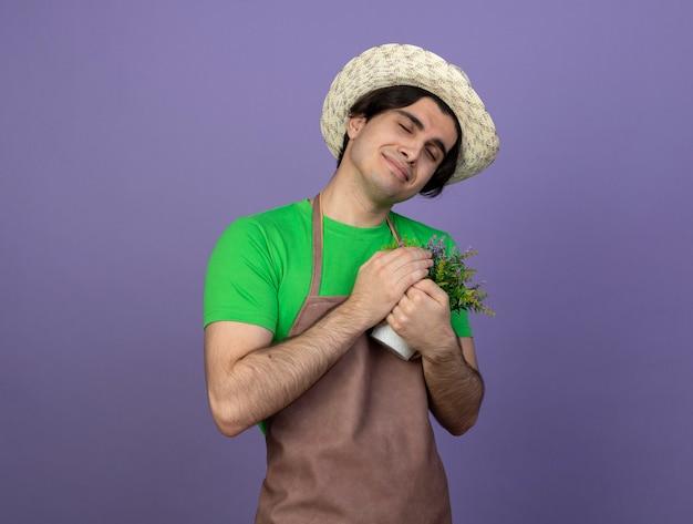 Наклоняя голову, доволен молодой садовник-мужчина в униформе в садовой шляпе, держащий цветок в цветочном горшке