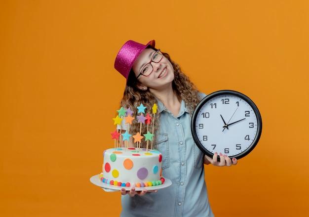Наклоняя голову, улыбающаяся молодая девушка в очках и розовой шляпе держит праздничный торт и настенные часы, изолированные на оранжевом фоне