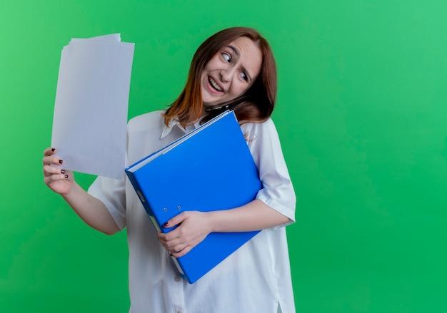フォルダーと紙を保持し、緑に分離された電話で話す若い赤毛の女の子の笑顔の頭を傾ける