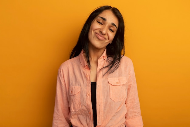 Testa di inclinazione dispiaciuta giovane bella ragazza che indossa la maglietta rosa isolata sulla parete gialla