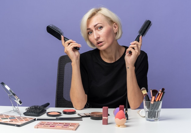 Tilting head young beautiful girl sits at table with makeup tools holding combs isolated on blue wall