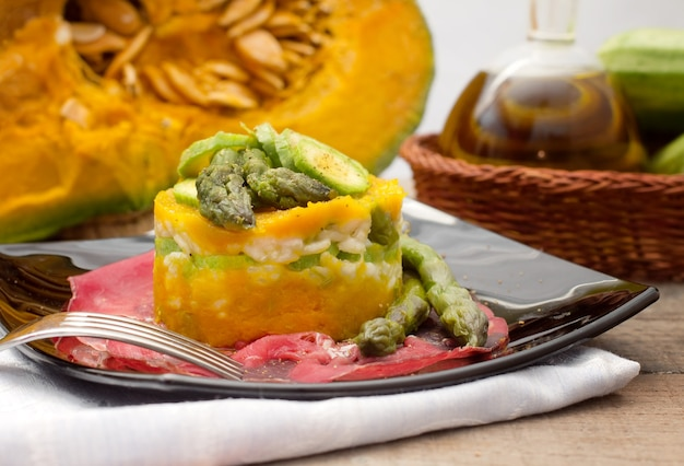 Timbale of rice and vegetable over bresaola slice