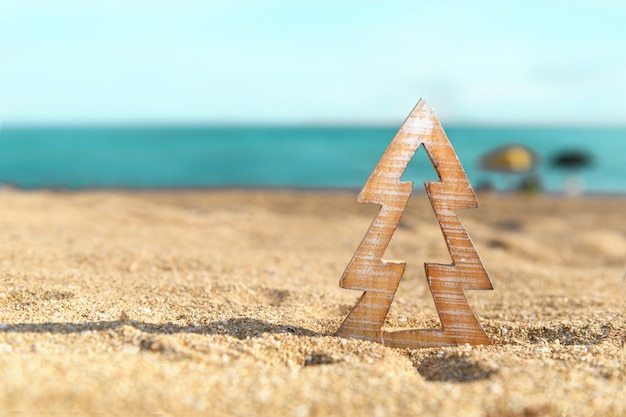 Timber wooden christmas tree on a sand on the tropical beach near ocean, summer christmas