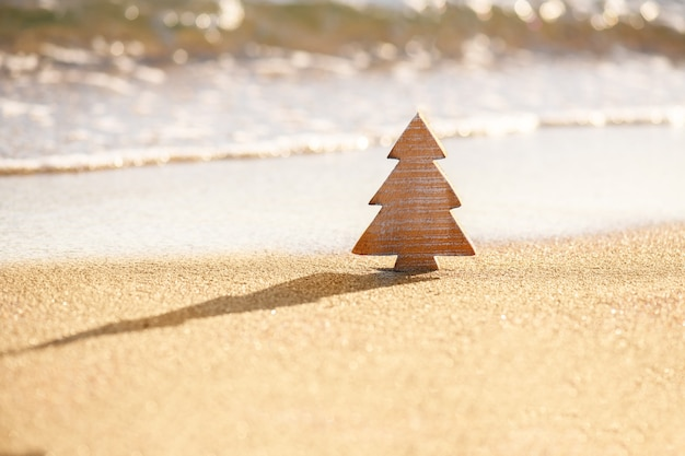 Timber wooden christmas tree on a sand on the tropical beach near ocean