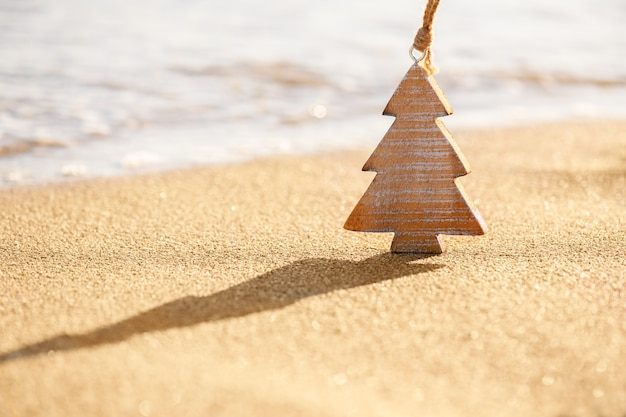 Timber wooden decoration of christmas tree on a sand on the tropical beach near ocean
