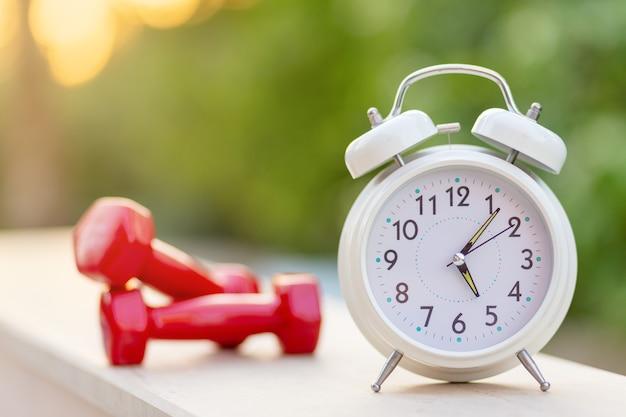 아침 5시 외부 녹색 자연 배경에서 알람 시계와 아령 운동