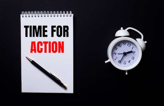Time for action is written in a white notepad near a white alarm clock on a black background