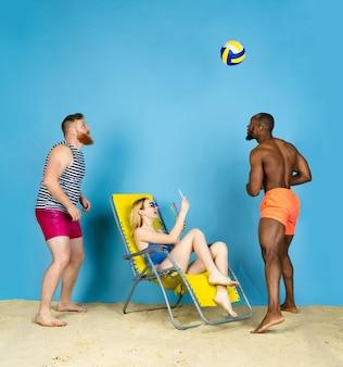 Tempo per l'attività. amici felici prendono selfie, giocando a pallavolo su sfondo blu studio. concetto di emozioni umane, espressione facciale, vacanze estive o fine settimana. freddo, estate, mare, oceano.