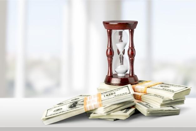 Изображение концепции времени и денег - песочные часы и фон денег.