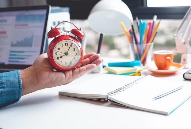 Концепция времени и работы с мужской рукой, держащей будильник на столе