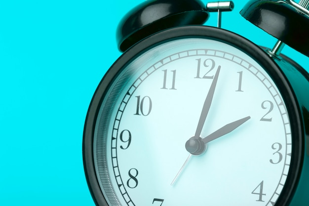Time background concept. vintage classic alarm clock on blue empty background. time management comcept