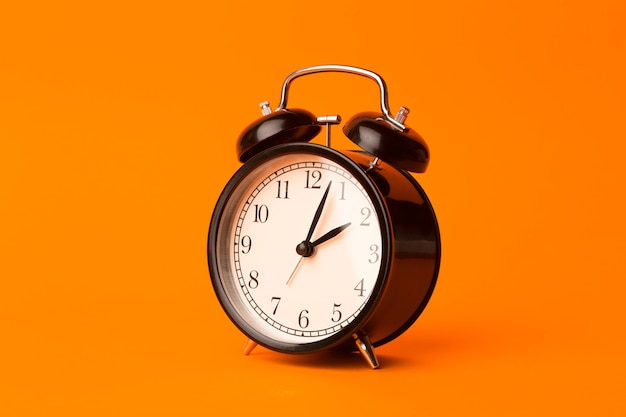 Time background concept. vintage classic alarm clock on orange empty background. time management comcept