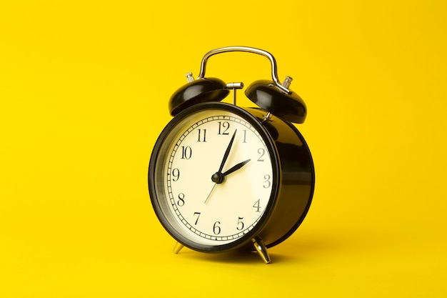 Time background concept. vintage classic alarm clock on yellow empty background. time management comcept