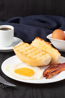 Time to breakfast with bread, bacon, egg and black coffee.