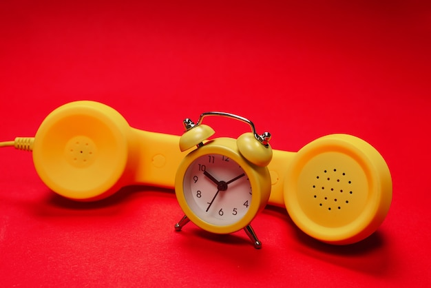 Time to call. yellow handset and alarm clock on a red background. copy space.