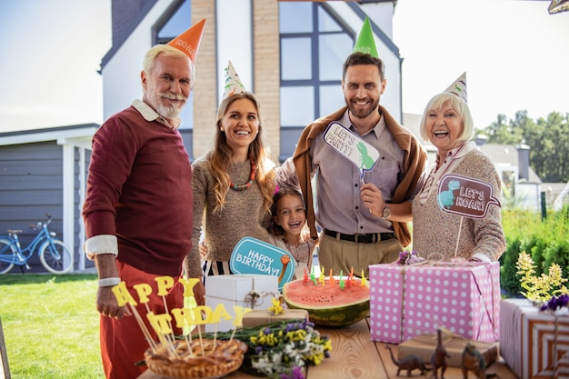 Time to celebrate. cheerful mature woman wearing paper hat while standing near her relatives