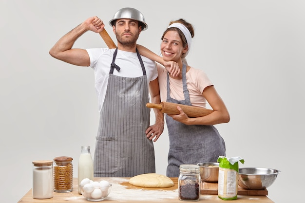 Time to cook. friendly cook team make dough, hold wooden rolling pins, feel tired but satisfied, pose at kitchen near table with necessary ingredients. woman and man participte in cooking contest