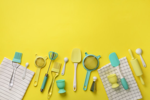 Time to cook. turquoise cooking utensils on yellow background. food ingredients