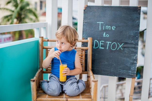 Time to detox chalk inscription. the boy is drinking fresh, healthy, drink made from fruits. fruit shake, juice, milkshake. health concept