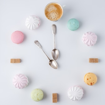 Time to drink coffee, a clock in the form of coffee, macarons, sugar, marshmallows