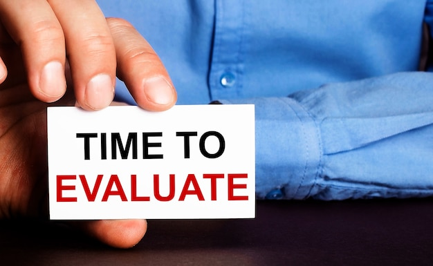 Time to evaluate is written on a white business card in a man's hand. advertising concept