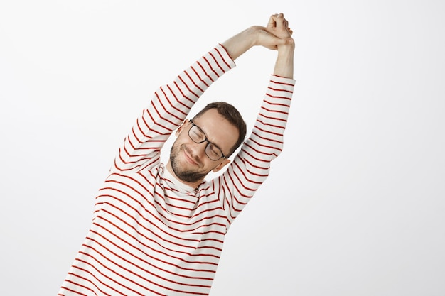 Time to do exercise for healthy body. portrait of tired and pleased attractive man with bristle in black eyewear, stretching with raised hands and tilting right