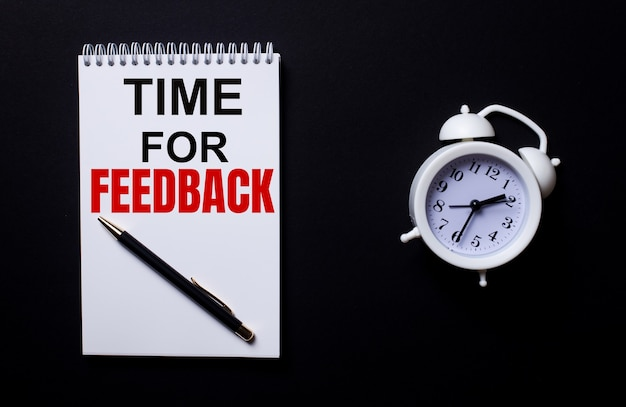 Time for feedback is written in a white notepad near a white alarm clock on a black surface.