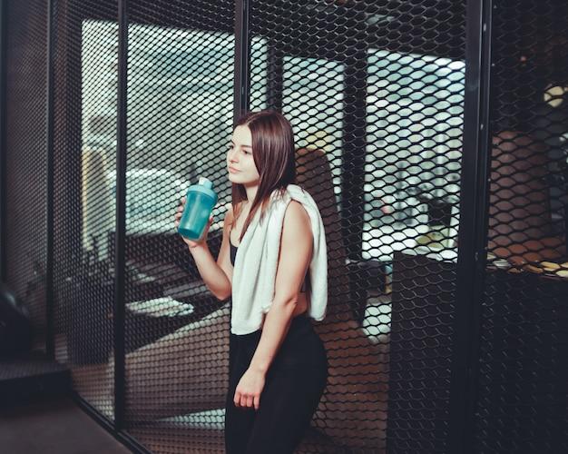 Время для перерыва. уставшая девушка в спортивной одежде пьет воду из бутылки с полотенцем