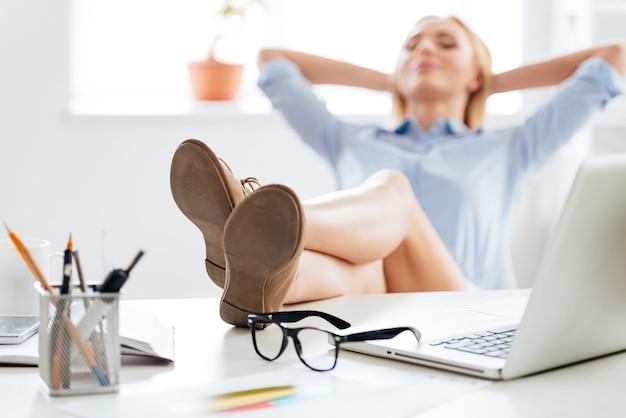 少しブレーキをかける時間です。彼女の頭の後ろで手をつないで、彼女の職場に座っている間、テーブルの上に足を維持している若い美しい女性のクローズアップ