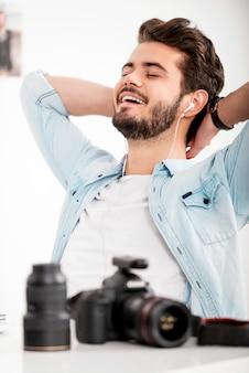 ちょっと休憩の時間。ヘッドホンで頭を抱えて、職場に座って笑っている陽気な青年