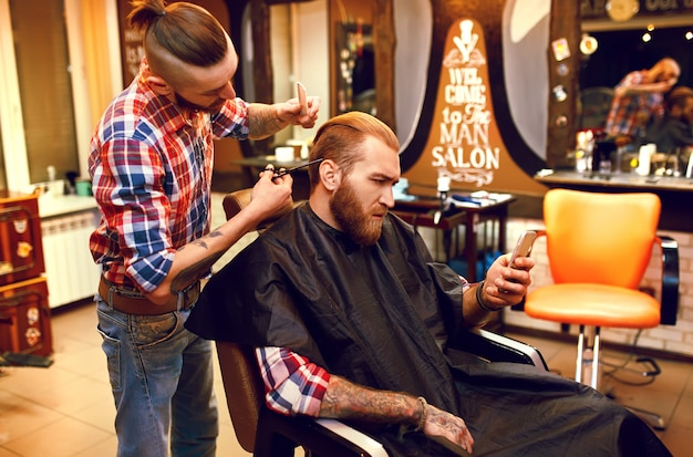 新しい髪型の時間です。ハンサムな若いひげを生やした男が散髪のために床屋に来ました。流行に敏感なスタイル。ファッションと美容のコンセプト。