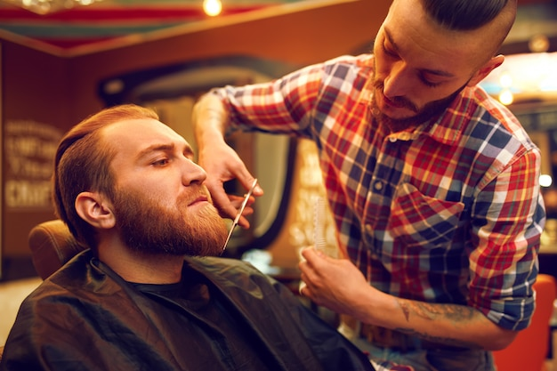 새로운 머리를위한 시간. 잘 생긴 젊은 수염 난 남자가 이발소에 이발을했습니다. 힙 스터 스타일. 패션과 뷰티의 개념.