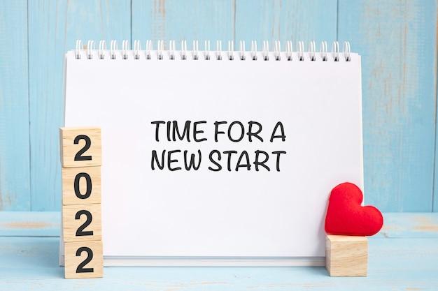 青い木製のテーブルの背景に赤いハートの形の装飾が施された新しいスタートワードと2022キューブの時間。新年newyou、目標、決意、健康、愛と幸せなバレンタインデーのコンセプト