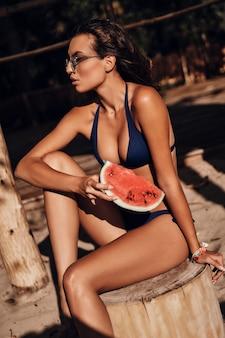 おやつの時間。屋外の木の切り株に座っている間スイカのスライスを保持している水着の魅力的な若い女性