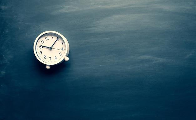 어두운 칠판에 시계와 함께 변화와 동기 부여 개념을위한 시간. 성공에 대한 사고 방식