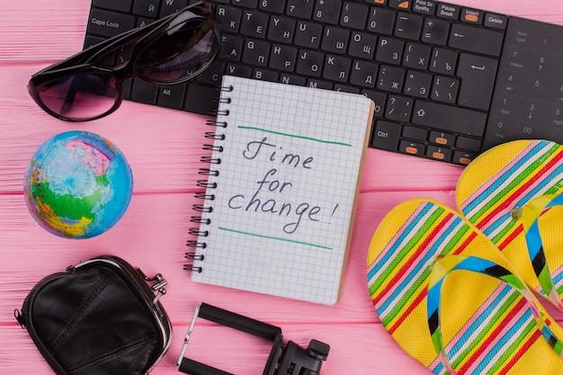 ピンクのテーブルトップの背景に女性の旅行者アクセサリーメガネ財布とビーチサンダルを備えたノートブックの変更の時間。グローブと黒のキーボード。
