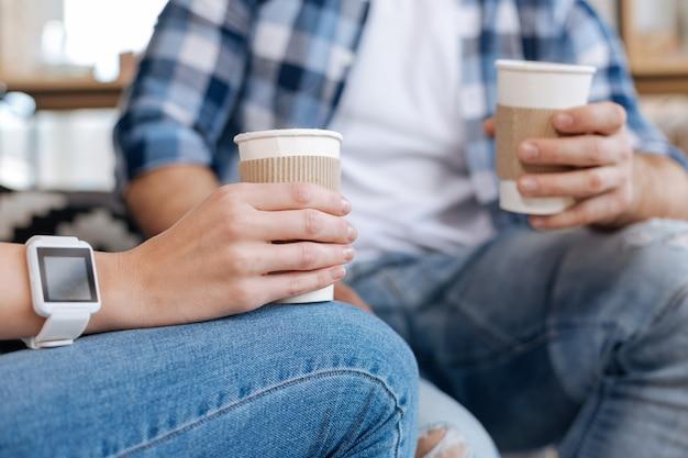 コーヒーの時間。コーヒーで満たされたプラスチック製のコップのクローズアップと仕事からの彼女の休憩を楽しんでいる間素敵な楽しい女性によって保持されています