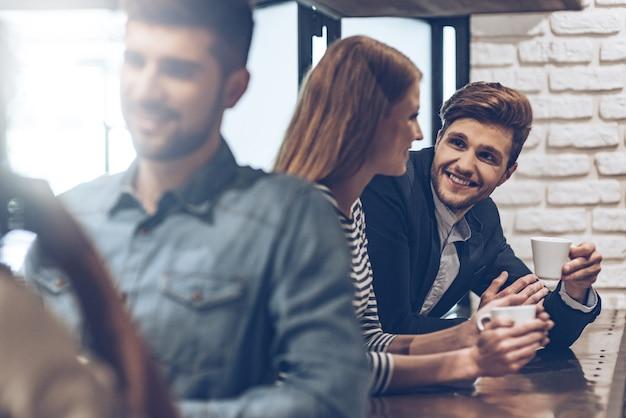 Время для кофе. вид сбоку на молодого красивого человека, держащего чашку кофе и обсуждающего что-то с молодой женщиной, стоя у барной стойки