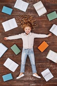 Время мечтать девушка лежит возле книг, смотрит в камеру и улыбается