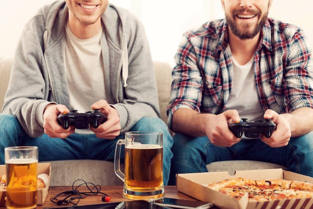 ゲームの時間。ソファに座ってビデオゲームをプレイしている2人の若い男性のトリミングされた画像